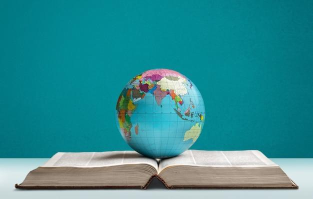 Livro pesado e o globo de um planeta na mesa