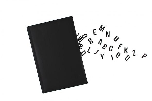 Livro preto com letras do alfabeto inglês.