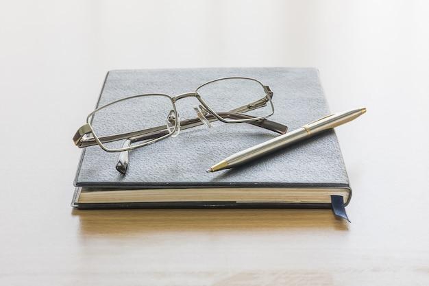 Livro preto com óculos e caneta
