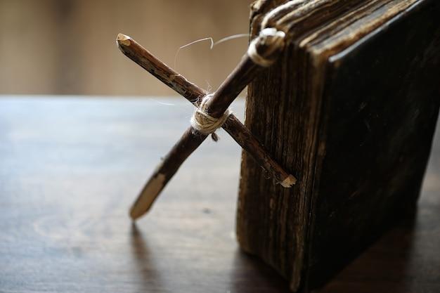 Livro religioso antigo e cruz de madeira no fundo de uma madeira e serapilheira