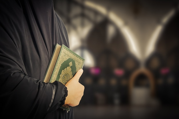 Livro sagrado dos muçulmanos (item público de todos os muçulmanos) alcorão na mão muçulmanos