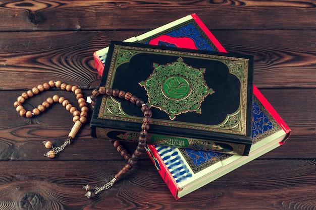 Livro sagrado islâmico na mesa de madeira com miçangas
