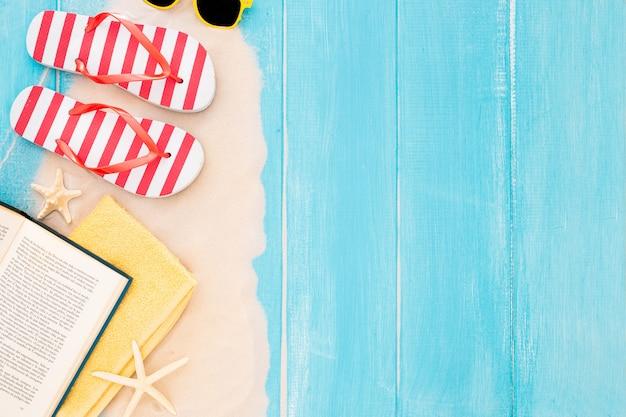 Livro, toalha de praia, flip flop, óculos de sol, areia no fundo de madeira azul