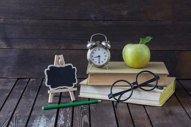 Livro, um lápis verde, um despertador, uma maçã verde, óculos e um quadro de escrever