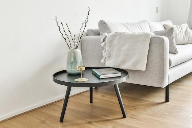Livro, vaso de planta, vela em uma mesinha de centro ao lado do sofá branco
