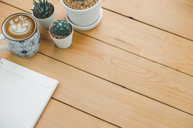Livro vazio e cappuccino quente em uma mesa de escritório de madeira marrom