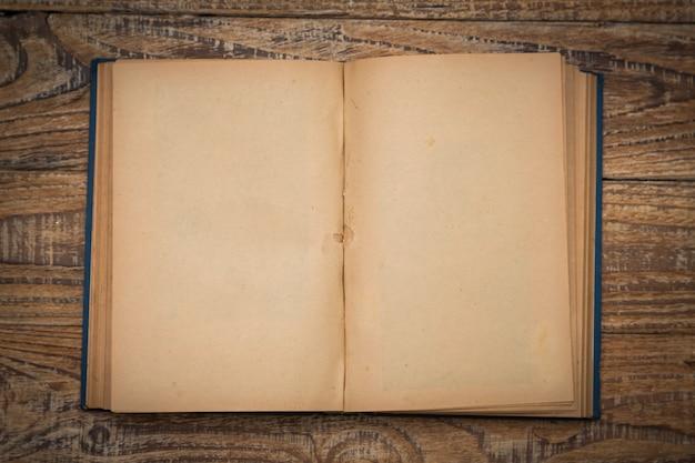 Livro velho aberto em uma mesa de madeira visto de cima