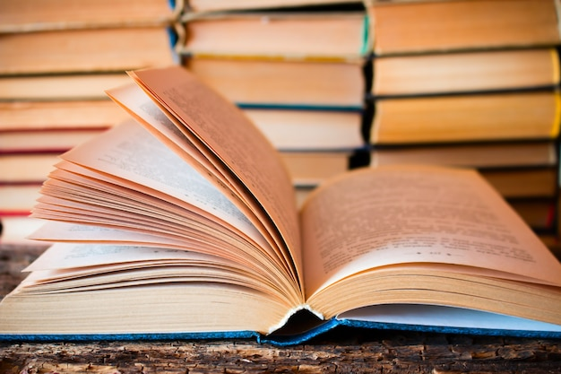 Livro velho aberto sobre a pilha de livros