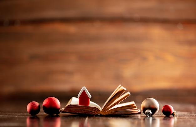 Livro velho com casa pequena e enfeites de natal na mesa de madeira
