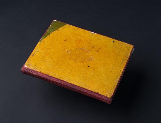 Livro velho e gasto em um fundo preto. livro manuscrito antigo Foto Premium
