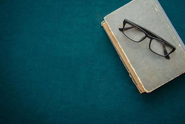 Livro velho e óculos em cima da mesa