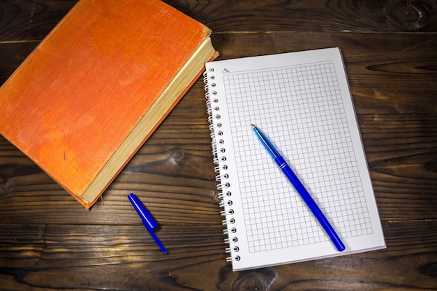 Livro velho fechado, bloco de notas e caneta na mesa de madeira