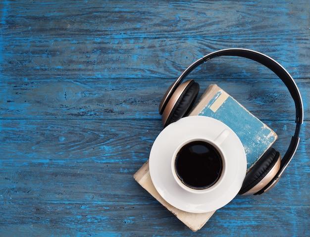 Livro velho, xícara de café e fones de ouvido no fundo escuro de madeira