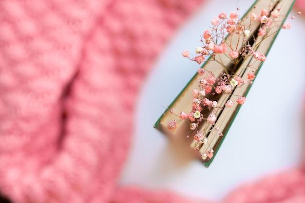 Livro verde com flores secas em um suéter de malha rosa quente