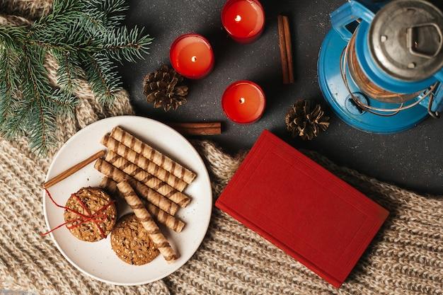 Livro vermelho, biscoitos em um prato e velas em um cobertor de malha.