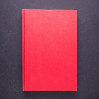 Livro vermelho com tampa vazia em branco sobre fundo preto mesa de pedra. vista do topo