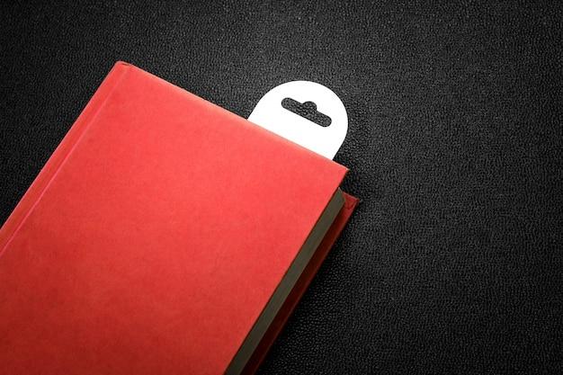Livro vermelho do vintage com um marcador no fundo escuro.