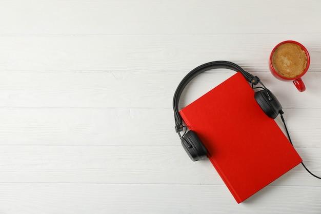 Livro vermelho, fones de ouvido e xícara de café no espaço de madeira, espaço para texto