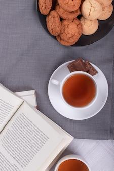 Livro, xícara de chá e chocolate em cima da mesa