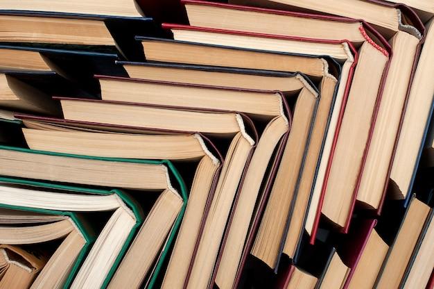 Livros abertos em uma pilha de livros de cores diferentes