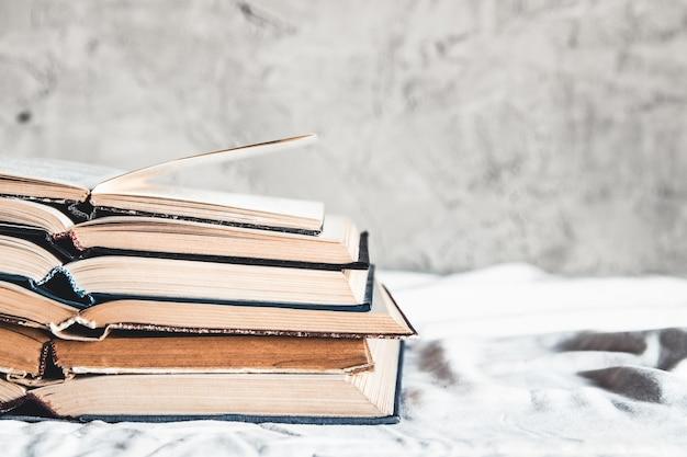 Livros abertos em uma pilha sobre um fundo claro em casa. educação, hobbies