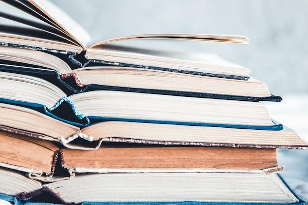 Livros abertos em uma pilha sobre um fundo claro em casa.