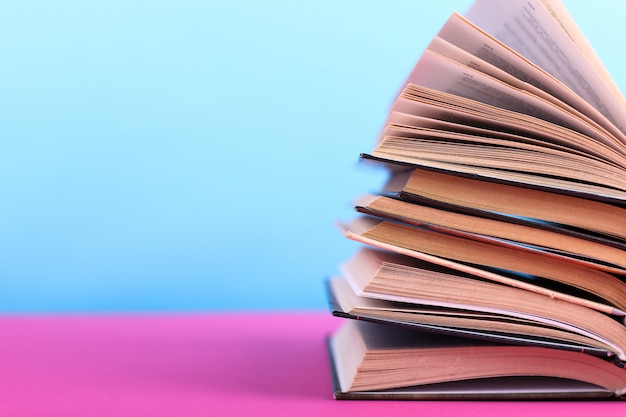 Livros abertos são empilhados sobre a mesa em azul. difícil lição de casa na escola, uma montanha de conhecimento.