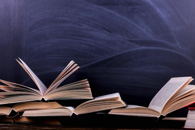 Livros abertos são uma pilha sobre a mesa, no contexto de um quadro de giz