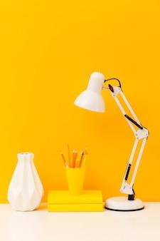 Livros amarelos e vista frontal da lâmpada de mesa