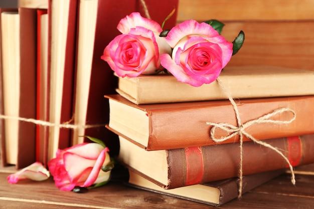 Livros amarrados com rosas cor de rosa na mesa de madeira, close