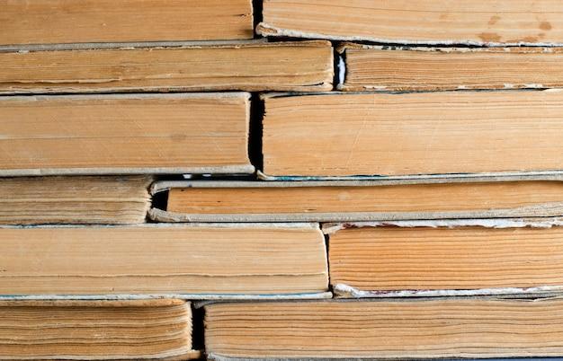 Livros antigos com capas amassadas e rasgadas.