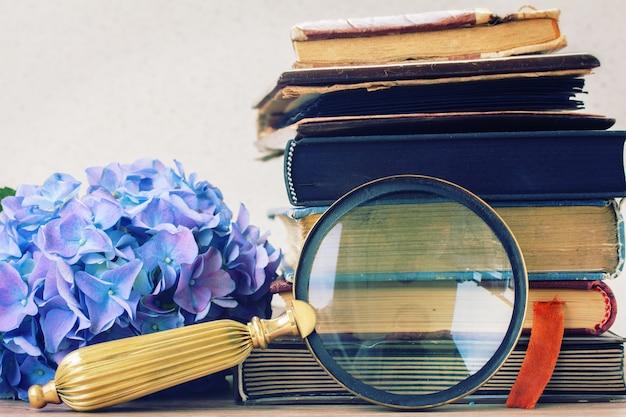 Livros antigos com flores azuis de hortênsia e vidro achatado