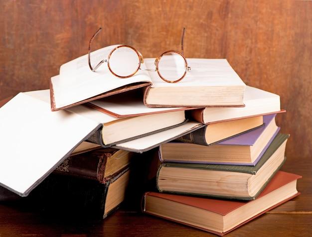 Livros antigos de capa dura e óculos vintage com lentes redondas em um fundo escuro