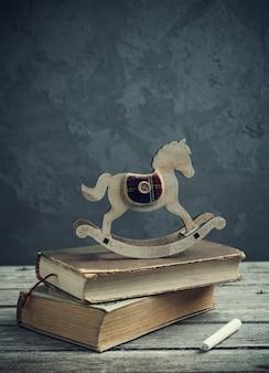 Livros antigos e cavalo de brinquedo de madeira