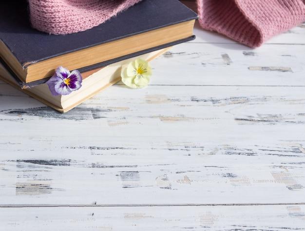 Livros antigos e flores na mesa de madeira clara. conceito de leitura. espaço de cópia livre.