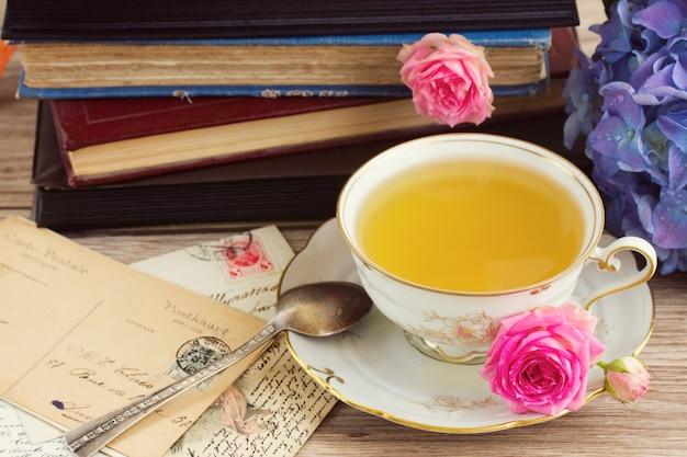 Livros antigos e pilha de correspondência com uma xícara de chá antiga