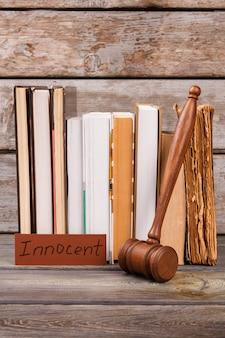 Livros antigos e veredicto inocente. martelo de madeira e livros tiro vertical.