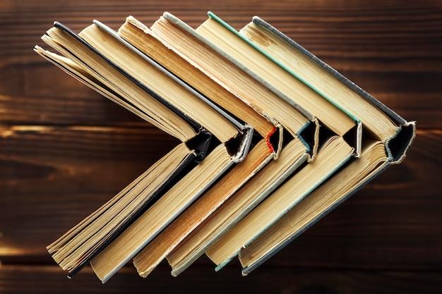 Livros antigos em uma linha em um fundo de madeira
