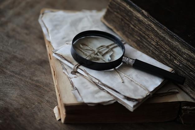 Livros antigos em uma mesa de madeira e lupa de vidro