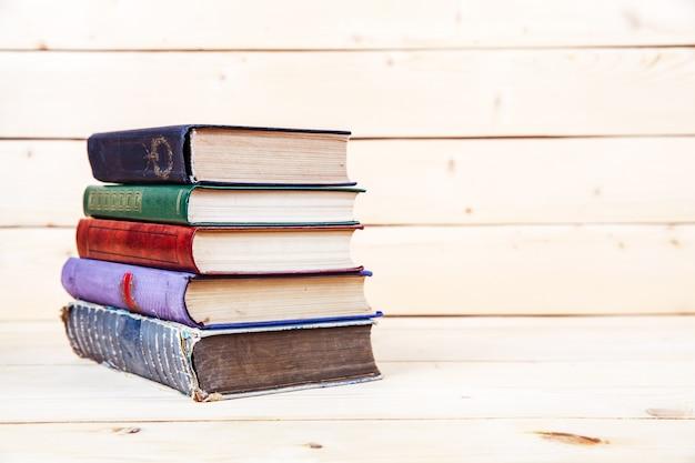 Livros antigos em uma prateleira de madeira.