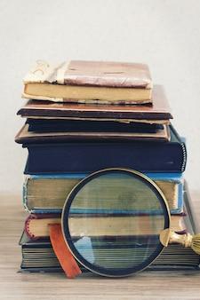 Livros antigos empilhados na mesa com achados de vidro