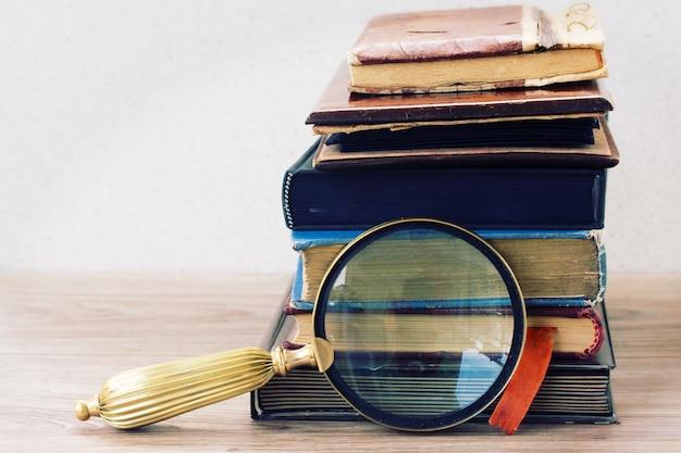 Livros antigos empilhados na mesa com vidros antigos