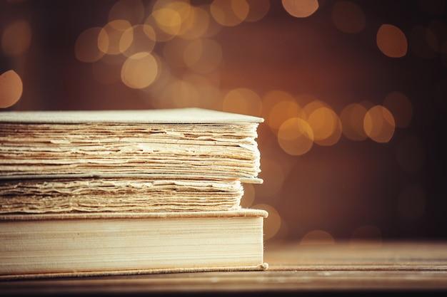 Livros antigos na mesa de madeira no fundo de luzes de fada