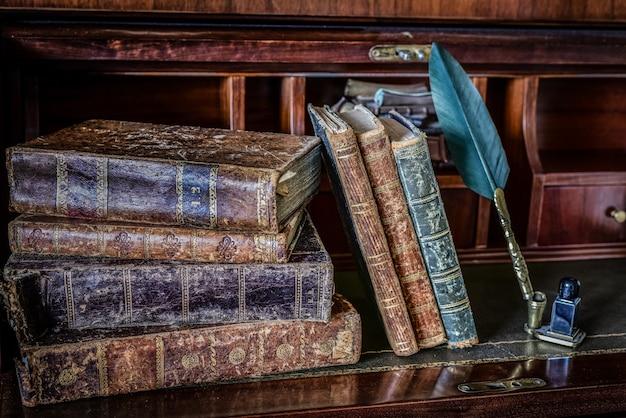 Livros antigos na mesa e escrita a caneta