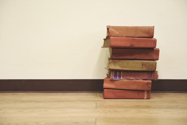 Livros antigos no chão de madeira pilha de livros na sala da biblioteca para negócios e educação, volta às aulas
