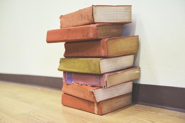 Livros antigos no chão de madeira pilha de livros na sala da biblioteca para negócios e educação