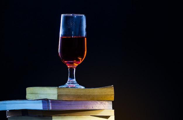 Livros antigos se sobrepõem em um fundo preto e com pouca luz um copo de vinho tinto no topo.