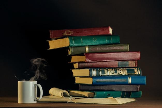 Livros antigos vintage e copo branco em uma parede escura