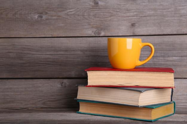 Livros antigos vintage e copo na mesa de madeira cinza