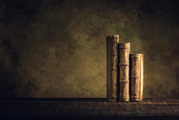 Livros antigos vintage no piso de madeira e papel envelhecido fundo ou textura